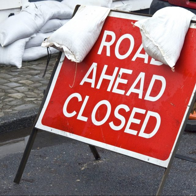 A road closed sign held down with sandbags following recent flooding in a Kent village UK. Other sandbags can be seen in the background protecting a property.