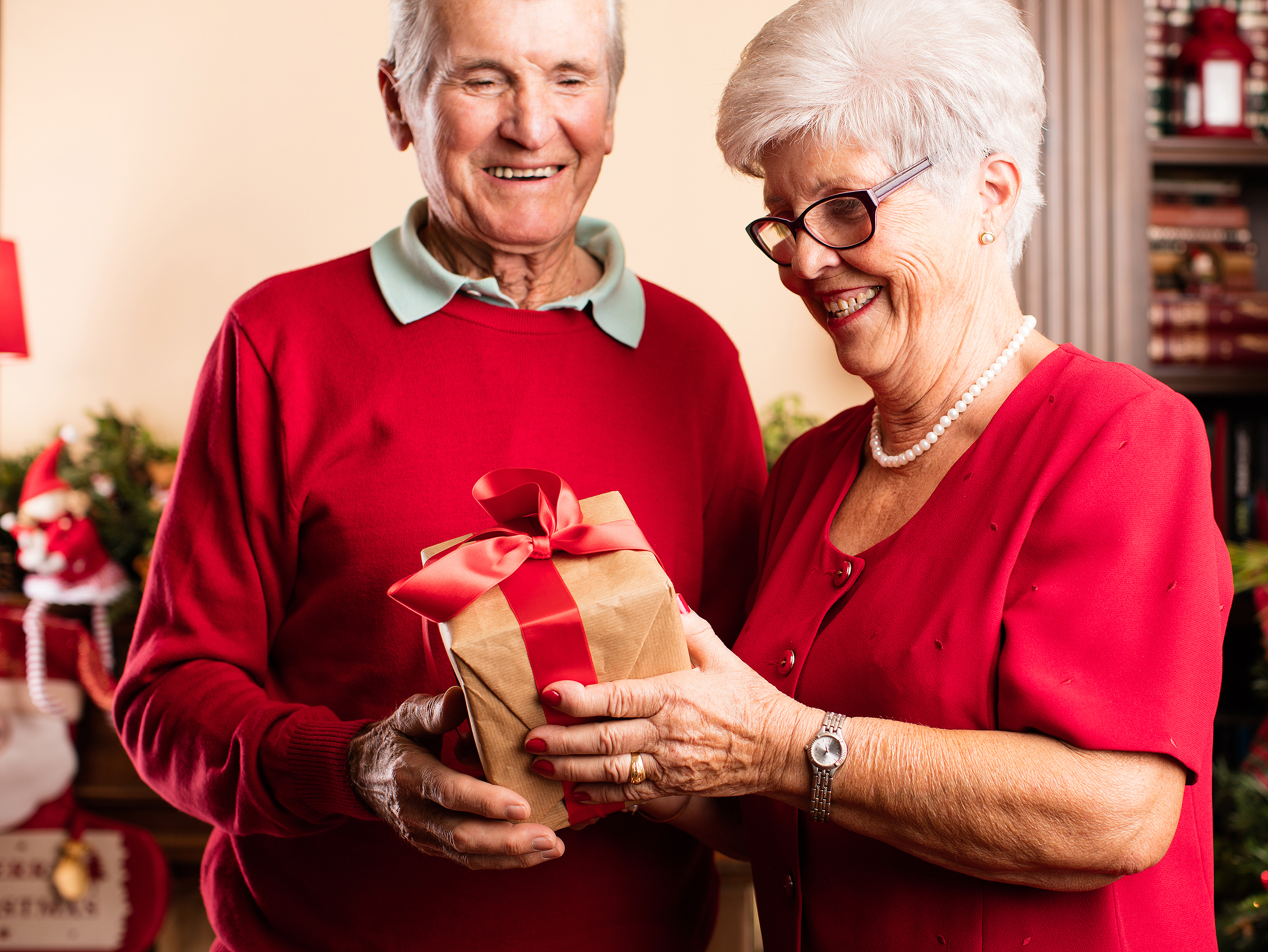 senior woman giving a present to her husband